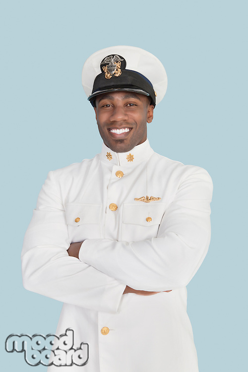 Portrait of a happy young US Navy officer standing with arms crossed over light blue background