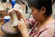 KUCHING, MALAYSIA - AUGUST 27, 2009: Unidentified woman cuts traditional tribal tattoo motives decoration at the raw kaolin in Kuching, Malaysia. Pottery made in Sarawak state of Malaysia at the island of Borneo with motives of traditional tribal tattoo is of two specific types - one done by the Iban, Murut and Kelabit potters and the other by Chinese potters. In our days the range of Sarawak's potters have improved and they create ceramic stools, drinking water cisterns, decorative jars, vases, lamps, candle holders, ashtrays, teapots, mugs and even photo frames.