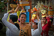 Women dressed in formal coroful clothing carry temple offerings in a procession during a temple ceremony in Ubud, Bali. Such ceremonies are a way of life for the Balinese.
