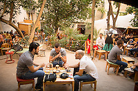 Athens, Greece- September 12, 2014: Friends chatting over freddo cappucinos at Six d.o.g.s., a multi-use artistic hub that features a spacious garden cafe and bar as well a space indoors for performances. CREDIT: Chris Carmichael for The New York Times