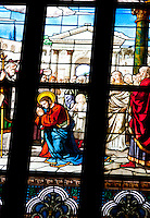 Milan, Italy, Duomo Cathedral. Stained glass window. Detail of a group of panes depicting the blessing of a holy man with halo in front of a crowd.