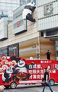 China, Sichuan. Chengdu. IFS Mall (Chengdu International Finance Square) is famous for the giant panda sculpture climbing up its wall. Two more hand painted pandas advertise the spicy food of Do Long Yi Hot Pot restaurant on an electric van.