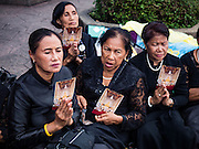 29 OCTOBER 2016 - BANGKOK, THAILAND: Women hold pictures of the Bhumibol Adulyadej, the King of Thailand, while they wait to go into the Grand Palace to homage to the King. Saturday was the first day Thais could pay homage to the funeral urn of the late Bhumibol Adulyadej, King of Thailand, at Dusit Maha Prasart Throne Hall in the Grand Palace. The Palace said 10,000 people per day would be issued free tickerts to enter the Throne Hall but by late Saturday morning more than 100,000 people were in line and the palace scrapped plans to require mourners to get the free tickets. Traditionally, Thai Kings lay in state in their urns, but King Bhumibol Adulyadej is breaking with tradition. His urn reportedly contains some of his hair, but the King is in a coffin,  not in the urn. The laying in state will continue until at least January 2017 but may be extended.       PHOTO BY JACK KURTZ