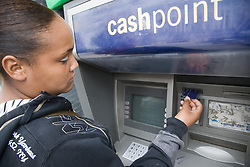 Teenaged girl withdrawing money from a cashpoint machine,