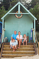 Vacationing Family sitting in beach hut portrait