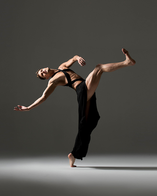 Contemporary male dancer, Andrew Brader, in a black dress. Taken in the photo studio on a dark grey background. Photograph taken in New York City by photographer Rachel Neville.