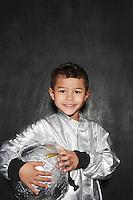 Portrait of young boy (5-6) in astronaut costume holding helmet smiling studio shot