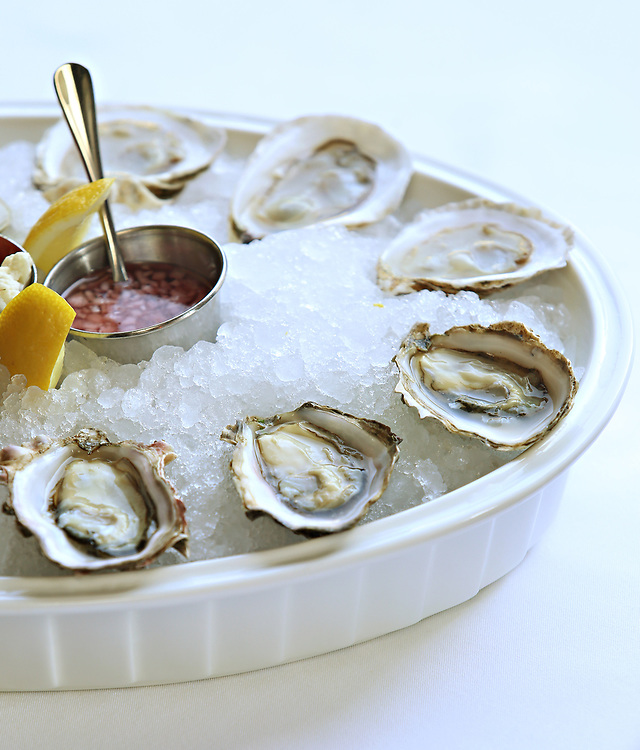 Buzzard's Bay oysters from Massachusetts, top, and Kusshi oysters from Washington state. Outside dining at the Clam, 420 Hudson Street, Monday, April 6, 2015. The restaurant features an outdoor oyster happy hour from 4:00 to 6:00pm. (Alexander Cohn for New York Daily News)