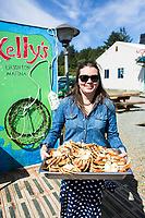 Young woman holding pan of Dungeness Crab at Kelley's Marina. Oregon Coast.