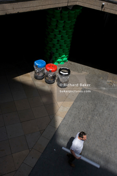 Three recycling bins seen from above in Southbank's pedestrian pavement.