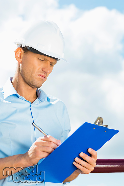 Male architect writing on clipboard against cloudy sky