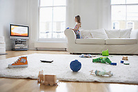 Girl (5-6) watching television toys on floor in foreground