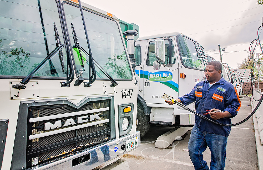 "Diesel mechanic Lawrence Henderson attaches a CNG-powered (compressed natural gas) Mack Truck to a time-fill station at Waste Pro, March 19, 2016, in Jacksonville, Florida. Waste Pro offers waste and recycling services to more than two million residential customers and more than 40,000 businesses in Alabama, Florida, Georgia, South and North Carolina, Louisiana, Mississippi, and Tennessee. The company has committed to ""going green"" by implementing a number of green initiatives, including using CNG (Clean Natural Gas) in its trucks, recycling more waste instead of sending it to landfills, and powering its regional headquarters throuh solar energy. (Photo by Carmen K. Sisson/Cloudybright)"