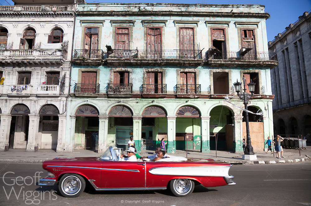 Immaculate 1959 Ford Edsel Convertible, passes run down buildings on the Paseo de Marti, Havana, Cuba