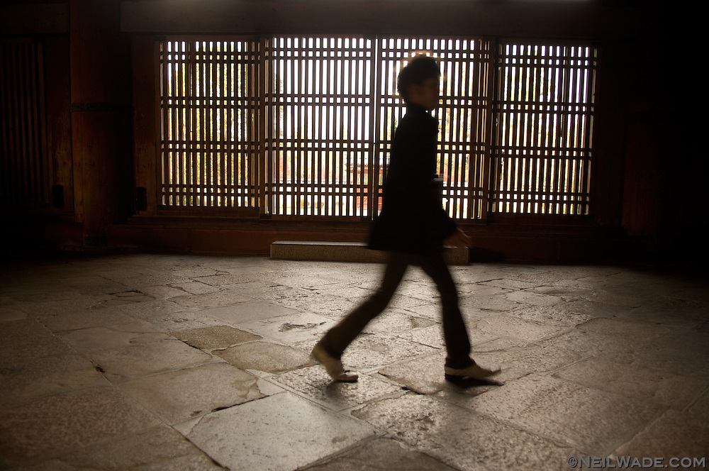 A man walks in front of Japanese style windows in Nara, Japan.