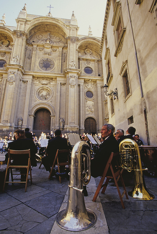 Europe, Spain, Andalucia, Granada, man with tubas playing in band in plaza by church