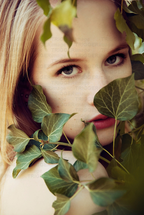 Close portrait of young woman partly covered by ivy looking into the camera