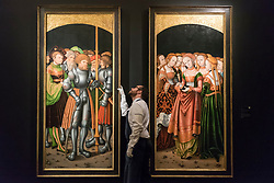 "© Licensed to London News Pictures. 29/11/2019. LONDON, UK. A technician inspects ""Wings from an altarpiece: Saint Achatius with a train of knights and nobles: and Saint Ursula with an entourage of maidens"", 1520-23, by Simon Franck (Est. GBP400-600k) at the preview of Old Masters sales at Sotheby's, New Bond Street.  Works will be offered for sale on 4 and 5 December.  Photo credit: Stephen Chung/LNP"