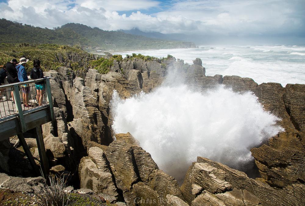 Tourists watching wave crashing up through Pancake Rocks, South Island, New Zealand