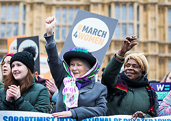 © Licensed to London News Pictures. 04/03/2018. London, UK. A woman dressed as a Suffragette raises her fist at March 4 Women which marks the centenary of the Representation of the People's Act 1918 by retracing the steps of the Suffragettes from Parliament to Trafalgar Square. Photo credit: Rob Pinney/LNP