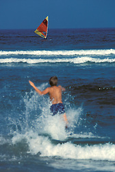Fun, sun and surf at the shore.  Young boy splashes into waves while windsurfer sails.