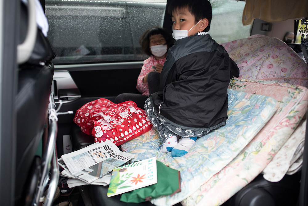 KUMAMOTO, JAPAN - APRIL 21: A family, survived from earthquake s seen in the car on early morning on April 21, 2016 in Mashiki Gymnasium parking area, Kumamoto, Japan. Over thousands of evacuees sleep in the car and survivors facing health threat, health experts says, 20 people diagnosed in Mashiki, one has died and 2 are in critical condition.<br /> As of April 45 people were confirmed dead after strong earthquakes rocked Kyushu Island of Japan. Nearly 11,000 people are reportedly evacuated after the tremors Thursday night at magnitude 6.5 and early Saturday morning at 7.3.<br /> <br /> Photo: Richard Atrero de Guzman