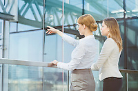 Businesswoman showing something to female colleague from glass wall in office