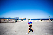 Een vrouw rent over de pier in San Francisco. De Amerikaanse stad San Francisco aan de westkust is een van de grootste steden in Amerika en kenmerkt zich door de steile heuvels in de stad.<br /> <br /> A woman runs at the pier in San Francisco. The US city of San Francisco on the west coast is one of the largest cities in America and is characterized by the steep hills in the city.