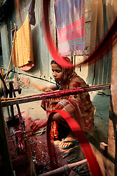 BANGLADESH SIRAJGANJ RADHUNIBARI 30JAN07 - Bangladeshi woman spins dyed cotton yarn onto small spools used in handloom weaving. Records of an indigenous weaving industry based on handlooms producing cotton fabrics date back to the 13th century in this area...jre/Photo by Jiri Rezac..© Jiri Rezac 2007..Contact: +44 (0) 7050 110 417.Mobile:  +44 (0) 7801 337 683.Office:  +44 (0) 20 8968 9635..Email:   jiri@jirirezac.com.Web:    www.jirirezac.com..© All images Jiri Rezac 2007 - All rights reserved.