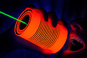 A man screams into glowing tin can phone.Black light