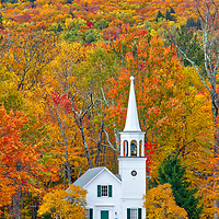 New England White Steeple Church framed by New Hampshire fall foliage colors framing. The iconic Wonalancet Union Church is located in Tamworth, New Hampshire. It was my first visit and approaching the location just blew me away. I quickly pulled over and explored certain perspectives and in this image made my way into the field with a wide angle lens. I loved how this classic New England Photography subject was framed by the colorful autumn foliage. <br />