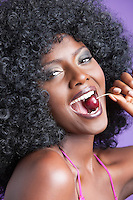 Close-up portrait of a flirtatious young woman with fizzy hair eating cherry