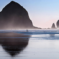 Haystack in Cannon Beach fully reflected in the sheen of low tide on the late afternoon beach sand. People out walking give it perspective. NIce subtle colors of blues and pinks and grays.