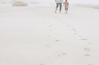 Father and Son Strolling on Beach