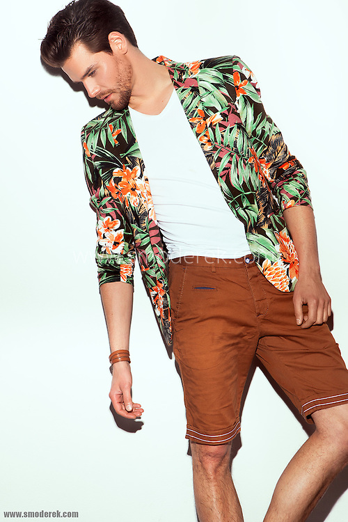 Fashion model in a editorial photoshoot with a flowery blazer by Zara and a pair of matching shorts.