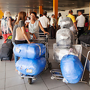 An American Airlines flight from Miami with mostly Cuban Americans arrive at Jose Marti airport in Havana carrying bulging suitcases and duffle bags with goods from the United Sates. Old classic cars wait to take the arriving passengers outside the arrivals terminal. <br /> Photography by Jose More
