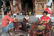 Balinese women putting finishing touches on wooden Budha statues in front of their shop in village of Mas. Many similar shops line the main street as individual Balinese villages specialize in specific types of craft like woodworking, painting, jewelry, etc. Their work is often produced for export.