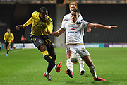 Coventry City forward Gervane Kastaneer (33) takes a shot at goal  under pressure from Milton Keynes Dons midfielder Jordan Houghton (24) during the EFL Trophy match between Milton Keynes Dons and Coventry City at Stadium:MK, Milton Keynes, England on 3 December 2019.