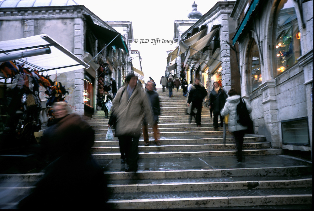 Pedestrians hustling up and down steps of the Rialto Bridge over the Grand Canal, Venice. Motion blur of those in the foreground..
