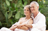 Middle-aged couple sitting outdoors cuddling portrait
