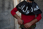 A Free Syrian Army fighter wearing a cloth that reads in Arabic ,'Mohammed is our prophet ' puts a grenade in his belt during a attack on government  forces  in Karm al-Tarib, near Aleppo's international airport.Aleppo, Syria August 17,2012. (Photo by Heidi Levine/Sipa Press).