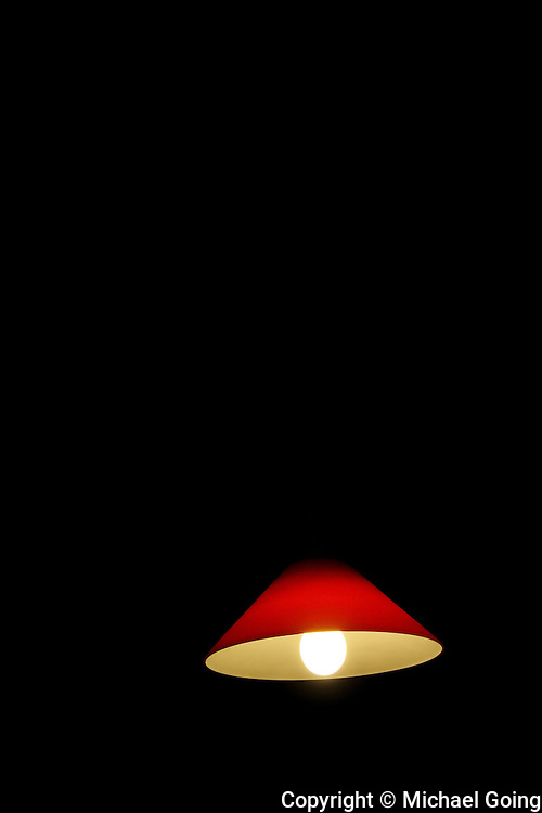 Vertical color photo of bright red hanging lamp with glowing bulb against black background