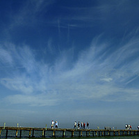 (02.02.2005)(PHOTO/CHIP LITHERLAND) -- As clouds feather across a blue sky, visitors walk the wood planks of the historic Anna Maria City Pier, built in 1910, on Anna Maria Island Wednesday morning.