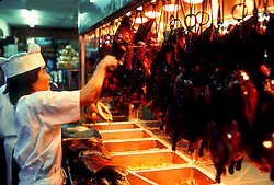 Stock photo of a man hanging freshly cooked meat to serve