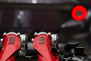 Detail of an engine of Ferrari car with logo and a tail light in background is seen on the photo from 84th Geneva car motor show.