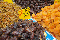 "Middle East, Israel, Jerusalem,  dates and other dried fruits on display at Mahane Yehuda Market (also known as Machaneh Yehuda), often referred to as ""The Shuk"", is popular with locals and tourists alike, the market's more than 250 vendors sell fresh fruits and vegetables; baked goods; fish, meat and cheeses; nuts, seeds, and spices; wines and liquors; clothing and shoes; housewares, textiles, and even Judaica."