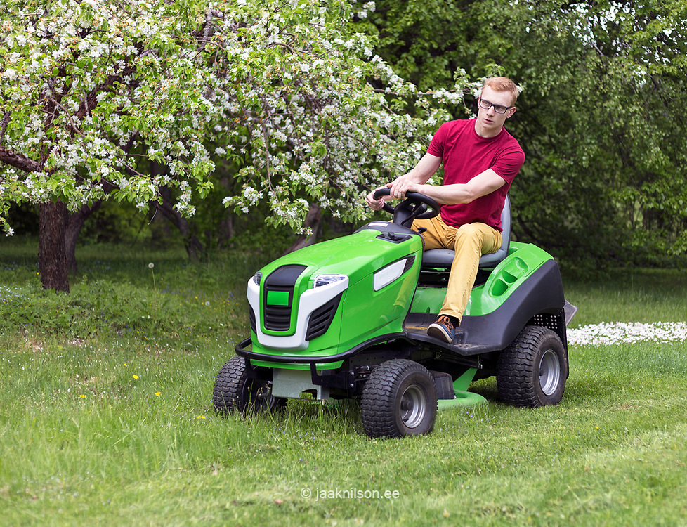 Young man, gardener driving ride on mower. Mowing grass in yard, tractor. Gardening.