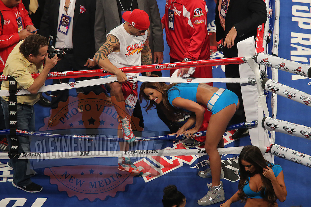 Miguel Cotto of Puerto Rico holds the ropes as a ring girl exits the ring  at the Amway Center in Orlando, Florida on Saturday, October 5, 2013. Cotto won by knockout in the 3rd round of the match.(Photo/Alex Menendez)