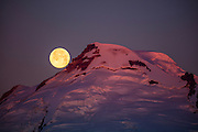 The full moon sets behind Mount Baker as the light of sunrise turns the peak of the volcano's cone red. Located in the North Cascades, Mount Baker, at 10,781 feet (3,286 meters), is the third largest volcano in Washington. It last erupted in 1880.
