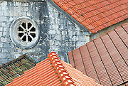 Elevated view of old and new roofs, with old church wall in background. Racisce, island of Korcula, Croatia.
